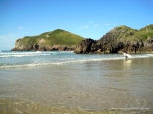 Surfers en Playa de San Martín e Isla de Poo en Llanes.